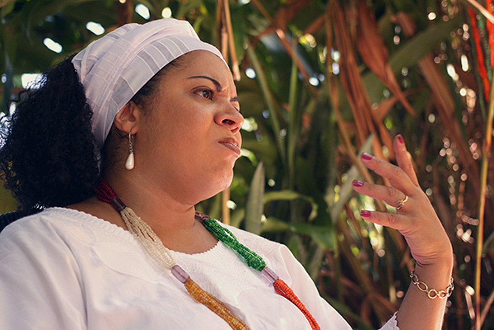 A black woman, age 39, some of her black hair wrapped in a white scarf, is gesticulating. She wears a white blouse and a necklace of colored beads. In the background, tall green and brown reeds are growing.