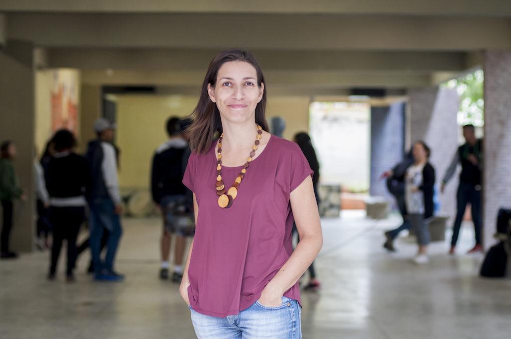 A foto mostra Cinthia Rodrigues, uma mulher magra, branca, aparentando 35 a 40 anos, cabelo castanho escuro, liso, à altura do ombro. Veste uma camisa de cor roxa e calça jeans. Está sorrindo para a câmera com as mãos no bolso. Ao fundo, vemos crianças correndo em um pátio da escola, desfocadas.