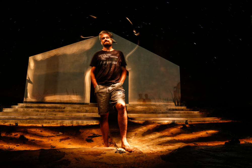 A man with a beard and slightly gray hair in his thirties. He wears a black T-shirt and shorts made from jeans. He is barefoot and looking at the camera with his hands in his pockets. Behind him seems to be a large shed with an entirely white wall. The night sky is visible.