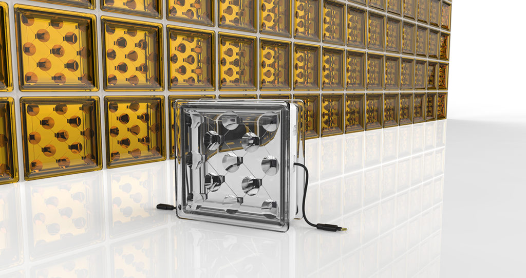 Yellow square bricks made of translucent glass line a wall, and their image is reflected in the surrounding interior, which, apart from the yellow bricks, appears to be entirely white. A similar but larger glass brick sits in front of them, a USB cable coming out its side.