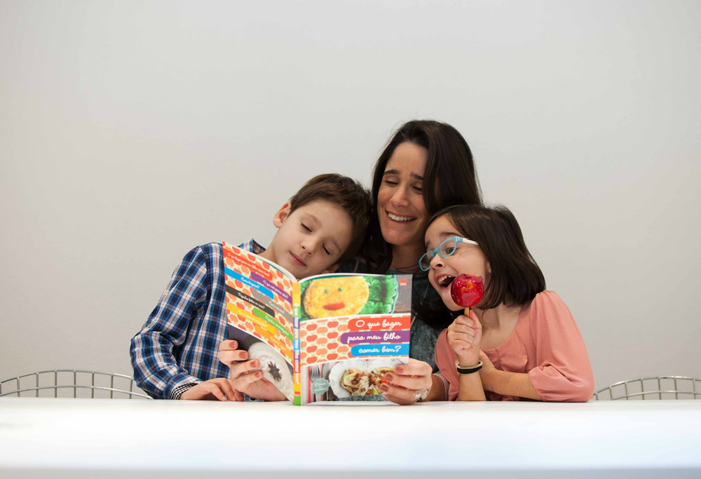 "A white woman with straight hair is sitting behind a white table (we only see the top of the table). She is holding open the book ""How Can I Get My Child to Eat Well?"" She is smiling and looking startled. There are two children, one on either side of her. A white boy, around the age of 7, rests his head on the woman's shoulder, his eyes closed. The other child, a girl with black straight and short hair, holds a candy apple and wears blue-rimmed glasses. They are all looking at the book together. The little girl's eyes and mouth are wide open as she notices, with delight, something on the page."