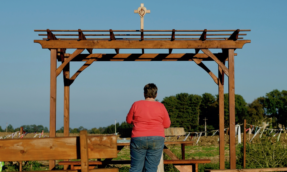 The picture shows a wooden open-air structure. There is a cross with a heart symbol on the roof. In the foreground there are some wooden benches. A woman with short brown hair wearing jeans and a long-sleeved pink shirt, her back to the camera, faces the wooden structure. She is praying. In the background, an open green area and some trees, all under a blue and cloudless sky