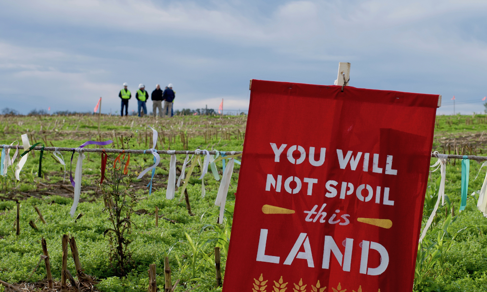 """A red flag with the inscription in English, """"You will not spoil this land"""" is planted in a green field in front of a fence. In the background, a group of four men, wearing clothes and safety helmets, are standing."""