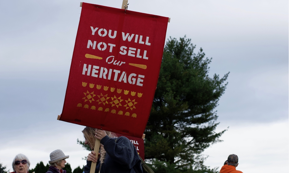 "A blonde woman (only part of her braided hair is visible, her face in profile) holds a red sign with an inscription in English: ""You will not sell our heritage."" In the background are trees and some older protesters."