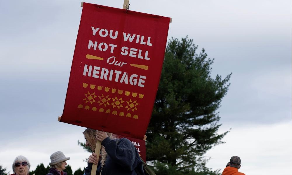 """Uma mulher loira (só vemos parte do seu cabelo e seu rosto de perfil), segura uma bandeira vermelha com a inscrição, em inglês: """"vocês não venderão nosso patrimônio""""."""