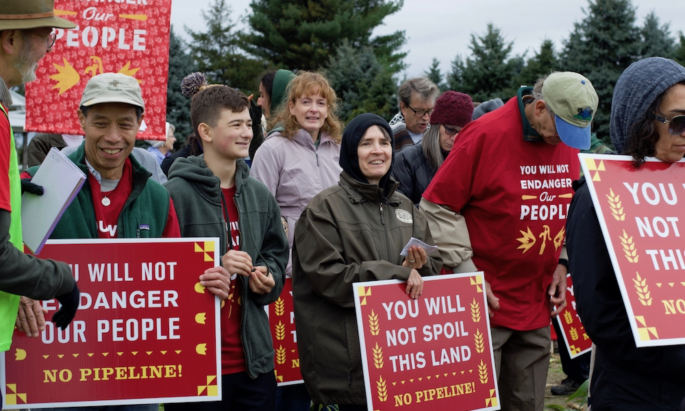 """A group of people of varying ages dressed for cool weather stand together, holding placards with inscriptions like, """"No pipeline!"""" """"You will not spoil this land,"""" """"You will not endanger our people."""""""
