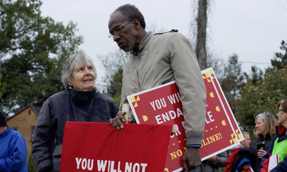 A tall black man, with gray stubble on his face, wearing glasses, is in conversation with to a shorter, gray-haired white woman. Both wear coats and are holding red protest signs. In the background are trees, and less distinctly, power lines.