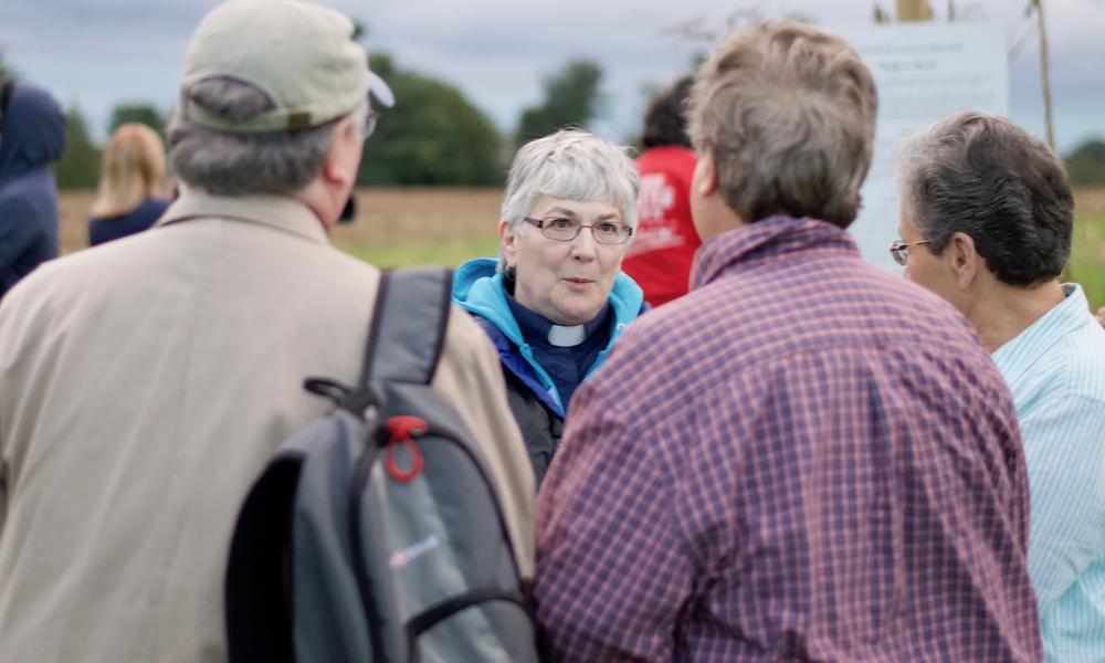 A lady with white hair and glasses talks with three other people, whose backs are turned to the camera.