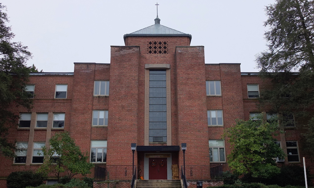 A three-story brick building, with a cross on the roof at its peak. At the entrance, a stairway of about ten steps offers access to the main door (the only one that appears in the image). The building also has a set of glazed windows and is surrounded by trees and shrubbery.