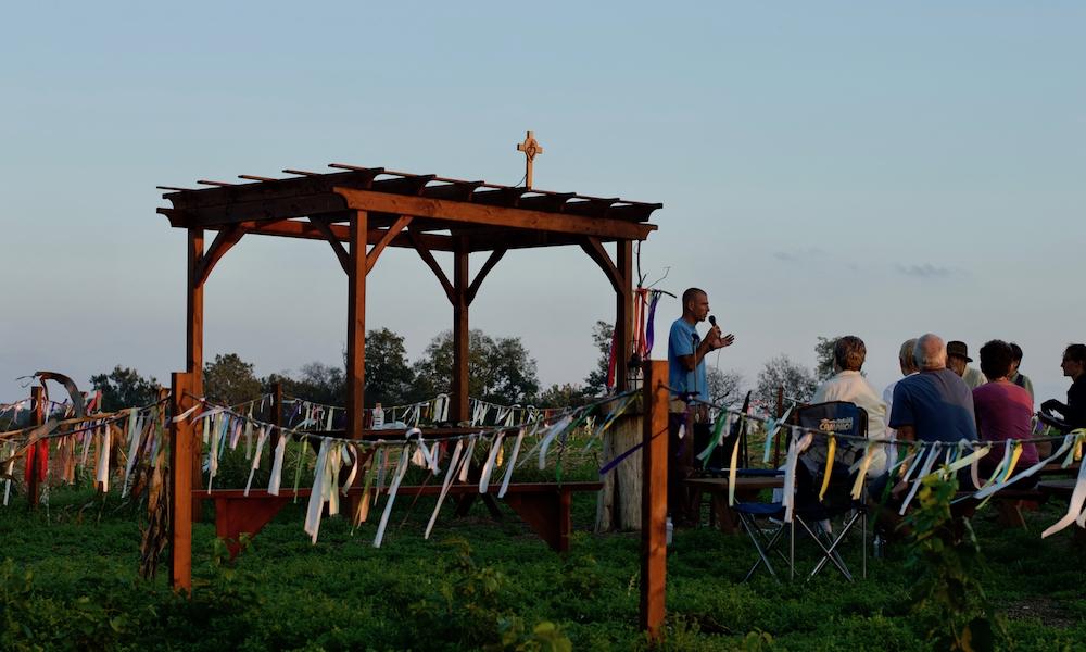 """A estrutura de madeira (a pequena capela a céu aberto descrita em fotos anteriores) aparece sob o céu azul em um fim de tarde. Ao redor, várias bandeiras coloridas. Ao lado, vemos um homem magro e calvo, segurando um microfone, e um grupo de pessoas mais idosas sentadas nos bancos de madeira da """"capela"""", olhando para ele."""