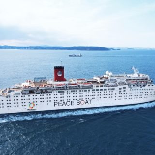 A large white cruise ship, with the phrase Peace Boat inscribed in its hull, sails through a blue sea under the cloudy sky.