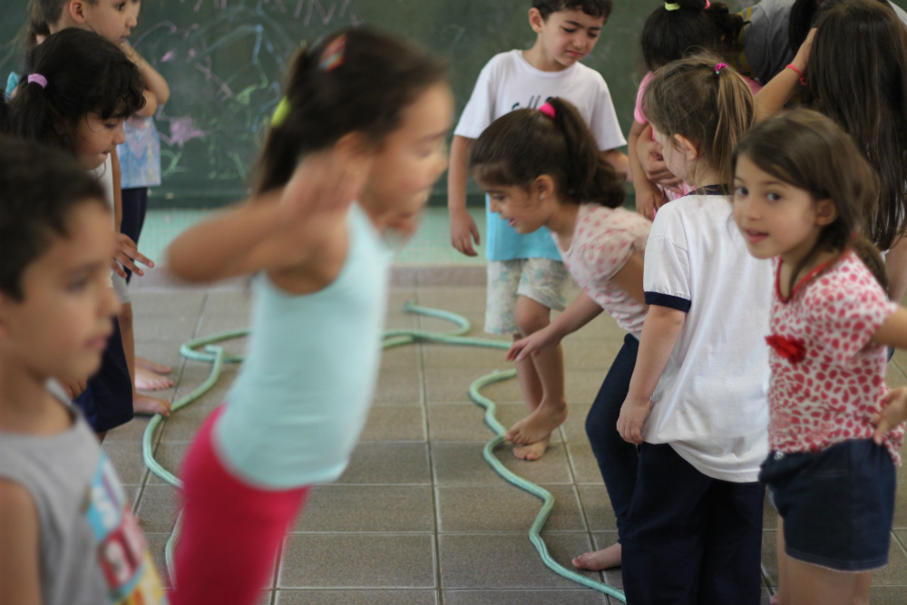 A group of seven elementary-school aged children in two rows, face to face. A rope on the floor separates them. One of them, blurry in the picture, is jumping over that rope.