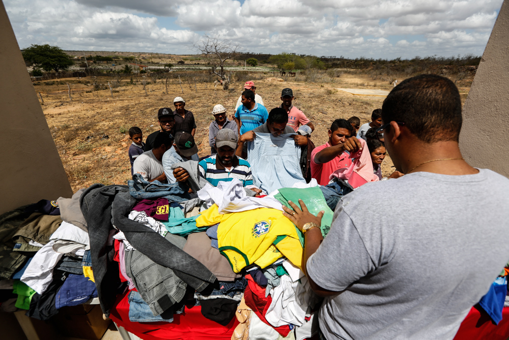 A dark-haired man, his back to the camera, wears a gray T-shirt. He stands behind a table full of clothing, including a yellow shirt for the Brazil national soccer team. A group, mainly of men, but including a woman and some children, looks at and chooses from the offerings on the table. There is an arid area in the background, and cloudy skies.