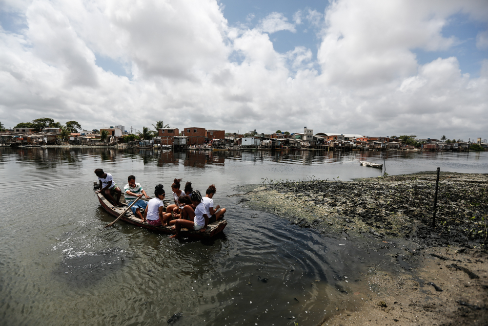 A group of 8 people is in a canoe, paddling in dark water. There is a small island with several simple houses of wood or masonry, built close together, in the background.