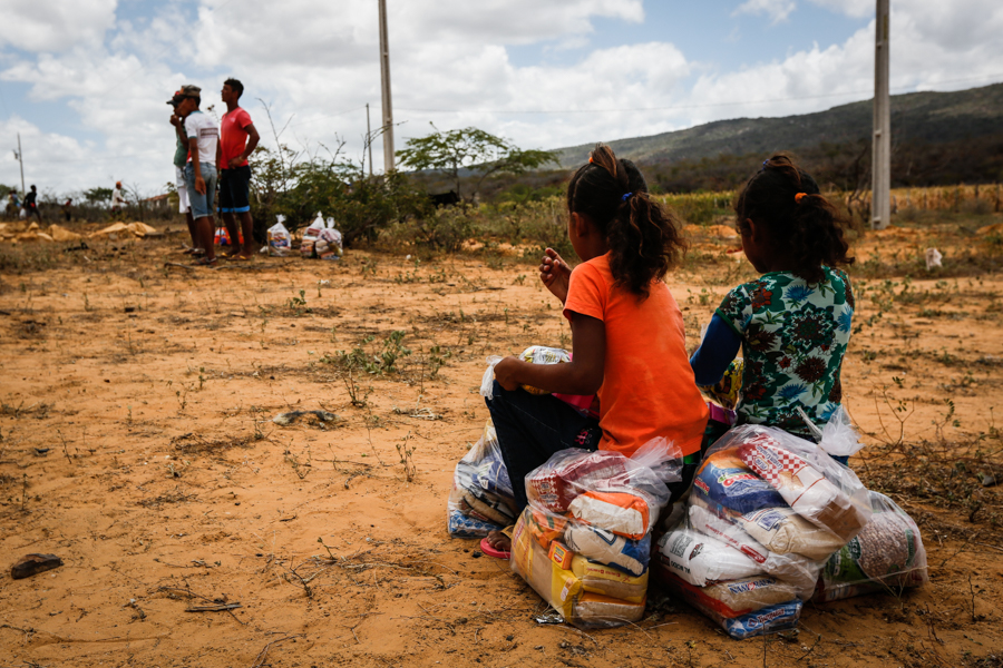 Two black girls, their backs facing the camera, sit on sacks of rice, flour and beans. Three older black boys look into the distance. The landscape in the background is arid, with little greenery. The sky is blue but cloudy.
