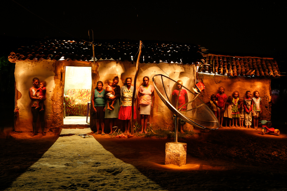 A night picture of a family in front of a mud house. There is a satellite dish in front of them. There are six women, two of them carrying children. Seven other children are lined up in front of the mud wall outside the house. A teenaged boy stands in between the women and children, slightly obscured by the satellite dish. All are posing for the camera.