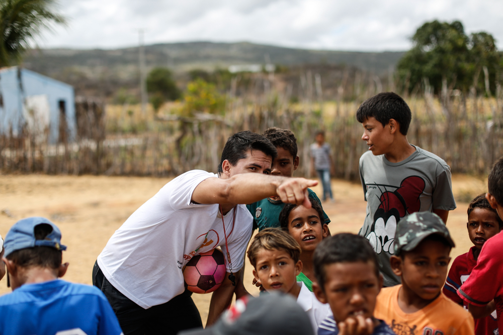 A group of boys between the ages of 5 and 10 is looking at something in the distance, in the direction that a grown man is pointing. This man holds a pink soccer ball and a whistle hangs from his neck. There is arid land with little greenery in the background.