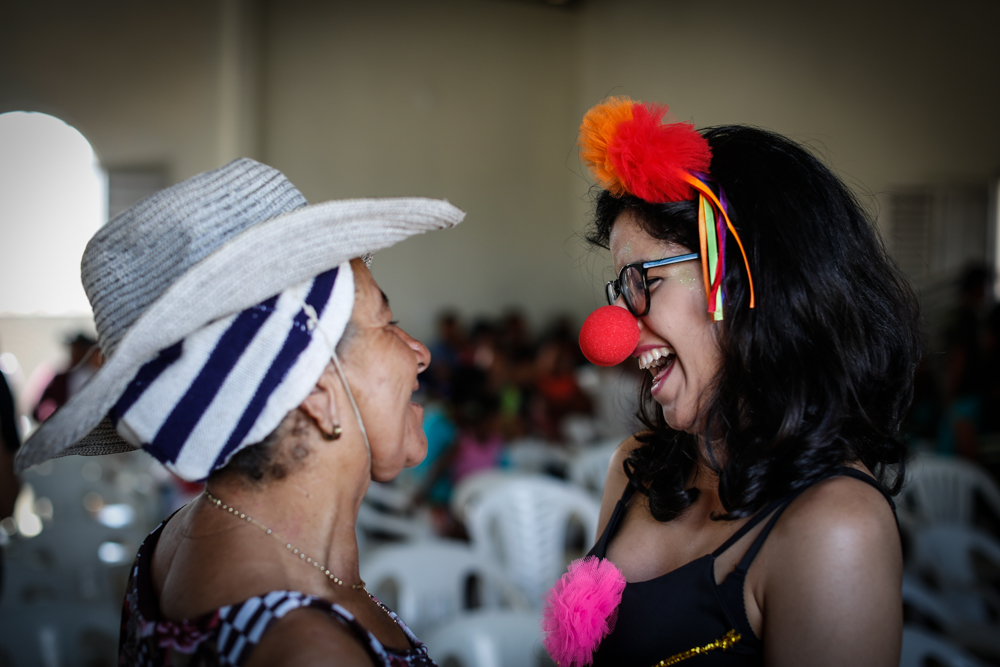 A young woman with black wavy hair is wearing colorful clown props: A tiara, a pink pin and a red nose. She is looking at an older woman. Both are smiling. The older woman wears a straw hat.