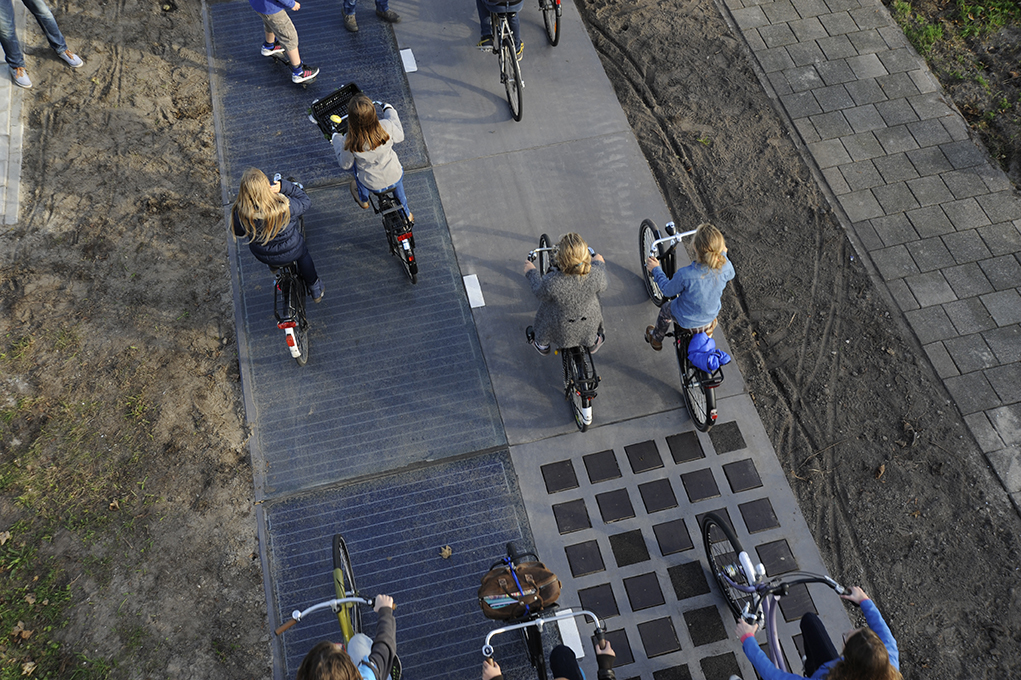 An aerial view of a group of about eight people riding bikes on asphalt. Part of the sidewalk is covered by a set of black squares.