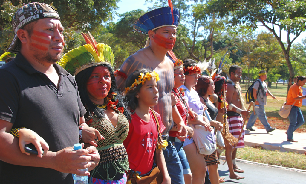 At least seven Indians, some adults and some children are walking in a row, in the street, arms linked. Some are wearing headdress, their faces painted. There are trees in the background, and a couple people pass by on the sidewalk.