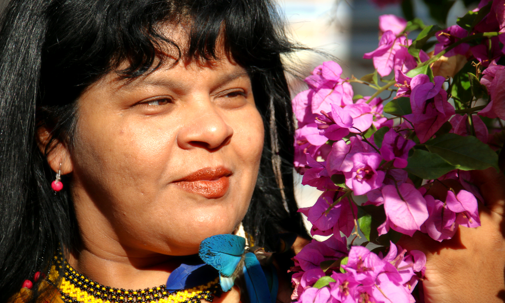 A black-haired woman, wearing an earring with a red bead, is looking happy, touching a bunch of flowers.