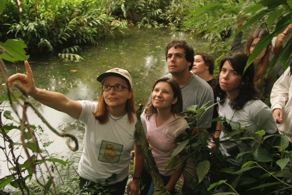 The photo shows a woman with brown hair down to her shoulders, wearing a cap, glasses, and a white shirt. She is pointing to a tree on a trail, next to a creek, followed by a few people who look in the direction she is pointing.