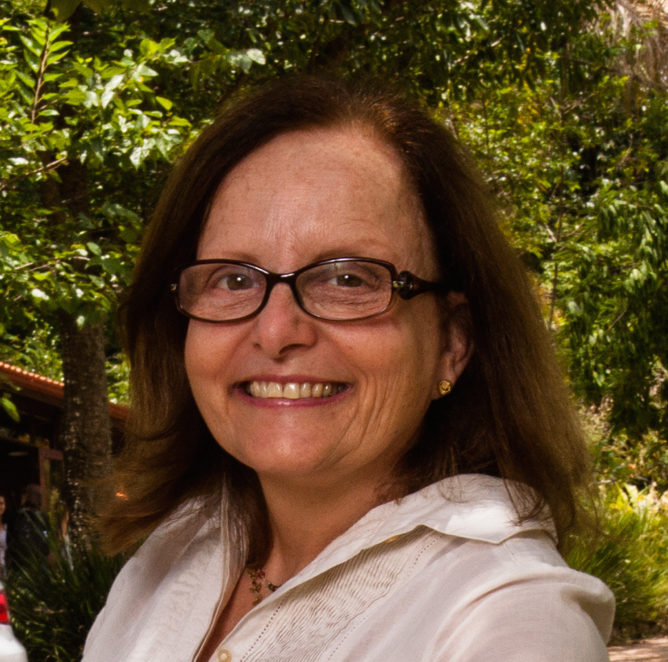 A brown-haired, shoulder-length woman with glasses and a white shirt, surrounded by green bush, looks smiling at the camera.