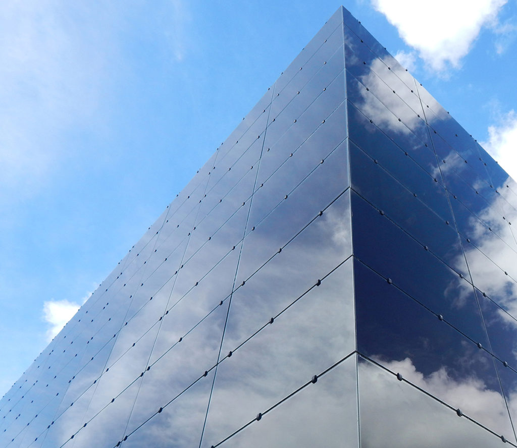 A close up, from outdoors, of the corner of a building made of rectangular glass blocks. The glass, already dark blue, reflects a blue sky with clouds. The view includes the top of the building.