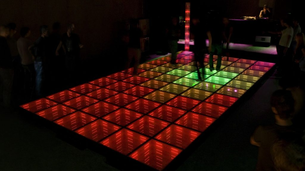 There is a rectangular dance floor formed by several colored squares, which light up in red, green and pink. On top of it, people are dancing, their images blurry.