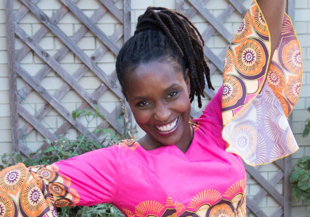 Una mujer sonríe a la cámara, con los brazos abiertos, pelo oscuro, con trenzas rasta, recogido en una coleta. Lleva un vestido rosa fucsia estampado en las mangas, de volantes, y debajo del pecho.