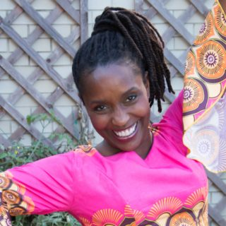 A black woman smiles, her arms open. Her black hair in dreadlocks tied into a ponytail, she wears a bright pink shirt with a bold orange and purple pattern on the ends of the sleeves and around her midriff.