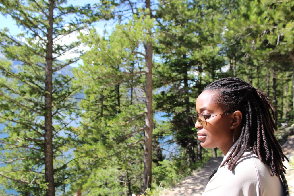 In the middle of a pine forest, a black woman in profile, wearing a cream-colored shirt and glasses, her hair in braids, looks ahead.
