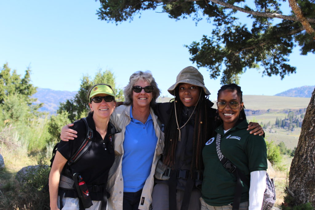 Four women are embracing, surrounded by trees, open space and sky. A white woman on the far left wears a green visor, sunglasses and a fanny pack. To the right of her is a second white woman, this one gray-haired, wearing a blue shirt and black sunglasses. To the right of her is a black woman with long braids wearing a brown hat. To the right of her is a second black woman, her braided hair tied back, wearing big glasses.