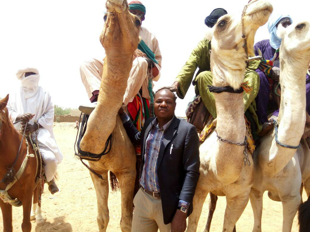 A bald black man, wearing beige pants and a black blazer, poses among three camels. On top of the camels are men wearing turbans, sitting on blankets. One rider's hand rests on the bald man's head. Beside them, a rider entirely in white, with bare feet, sits on a horse.