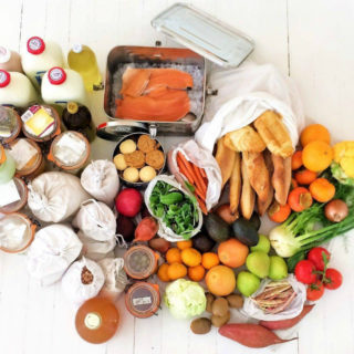 A view from above of groceries laid out on a white wooden table: bottles of milk, glass jars of food, and a cloth bag full of baguettes. One aluminum container contains pieces of salmon, and another holds cookies. There is also fruit (oranges, tomatoes, avocados, kiwis, pears) and assorted vegetables, including a cauliflower and some potatoes.