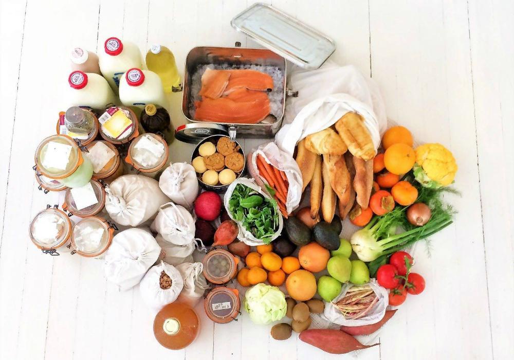 Imagem vista de de cima, com várias alimentos expostos em uma mesa de madeira branca. Há garrafas de leite, potes de vidro com mantimentos, um saco de pano com baguetes, uma lata de alumínio com pedaços de salmão, outra contendo cookies, frutas (laranja, tomate, abacate, kiwi, pêra) e legumes variados (couve-flor, batatas...)