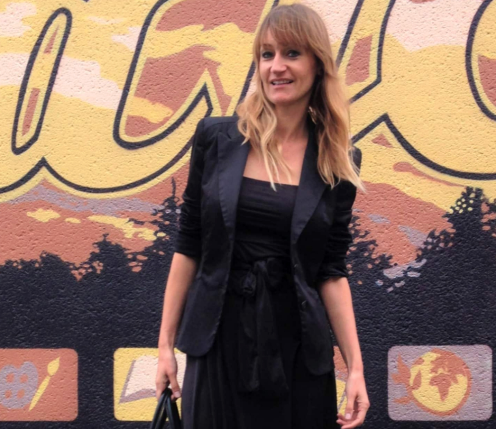 A thin, white woman, with chest-length blonde hair and bangs, wears a black dress and matching black jacket. She smiles at the camera. Behind her, painted on a wall, is a mural depicting an orange and yellow sky, with trees in silhouette.
