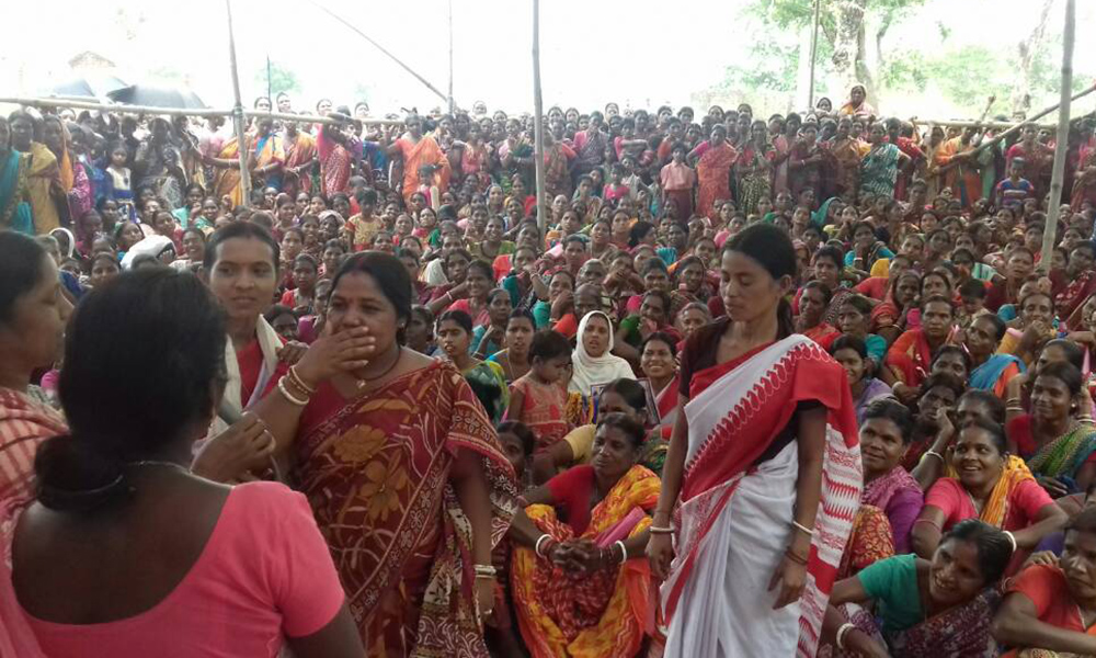 Hundreds of Indian women with brown skin wearing long and colorful sarees (typical dresses of their culture). Most are seated and, in the foreground, some are standing. They seem to be attending an outdoor performance or rally.