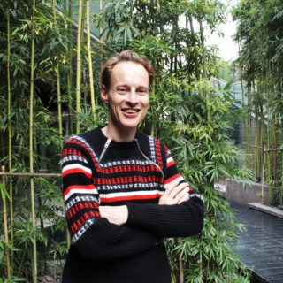 A thin, white man with straight, blond hair is smiling at the camera. He is standing with his arms folded. He wears a black wool sweater with red and white stripes across the chest. In the background is part of a walkway lined with trees.