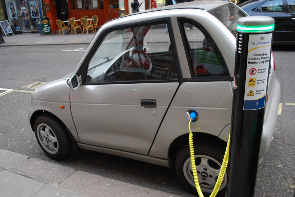 "On a street, a small, silvery-colored electric car plugged with a cord into a pole. On the pole is written, ""City of Westminster, Elektrobay Electric Vehicle Recharging Site."""