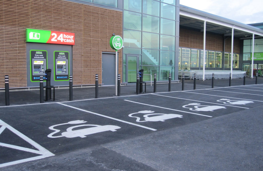 An empty supermarket parking lot, with several parking spaces marked, on the asphalt, by images of cars wired with plugs. In front of some of the parking spaces are small poles with blue outlets.