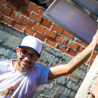 A brunette man, wearing a white T-shirt, a blue and white cap, and glasses with black rims, looks directly at the camera and smiles. His left hand rests on the arm of a photovoltaic panel, which is attached to a building's exterior. His other hand is at his waist. Behind him is an exposed brick and concrete wall.