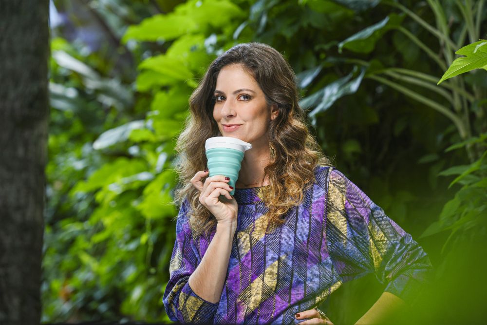 A thin, white woman with light-brown, wavy hair, wearing a long-sleeved shirt printed with a pattern of blue, lilac and yellow parallelograms, poses with her left hand on her waist. In her right hand, she holds a recyclable cup. Her nails are painted with a dark red polish. She looks at the camera and smiles.