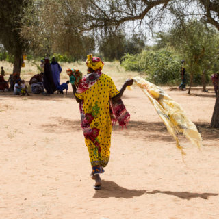A black woman is wearing a long dress and a colorful turban (yellow with a red and green print), in the middle of the image, her back to the camera. She holds a yellow scarf and walks toward a group of about 15 black people gathered in the shadow of a tree. The land is desert, with sand and few trees.