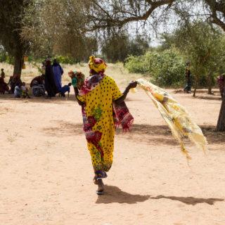 Una mujer negra, lleva puesto un vestido largo y un turbante colorido (amarillo con estampado rojo y verde), está en el centro de la imagen, de espaldas, sosteniendo un pañuelo amarillo y corriendo hacia un grupo de unas 15 personas negras que están bajo la sombra de un árbol. El terreno es desértico, con suelo de arena y algunos árboles.