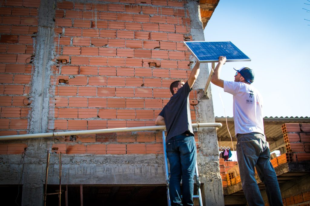 The image shows the brick exterior of a building, where two slender men wearing jeans and t-shirts are installing a small (less than 1 square meter, or 3.2 square feet) photovoltaic panel. They hold the board and stand with their backs to the camera.