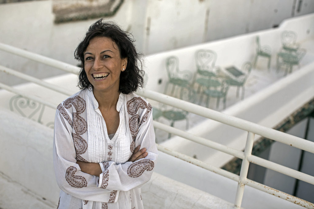 A smiling woman with brown, shoulder-length hair, her arms crossed. She wears a white tunic. She is standing on a balcony with a white parapet and white railing.