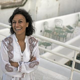 Uma mulher sorrindo, de braços cruzados, cabelos castanhos na altura dos ombros, bata branca, em uma varanda com parapeito e grades brancas.