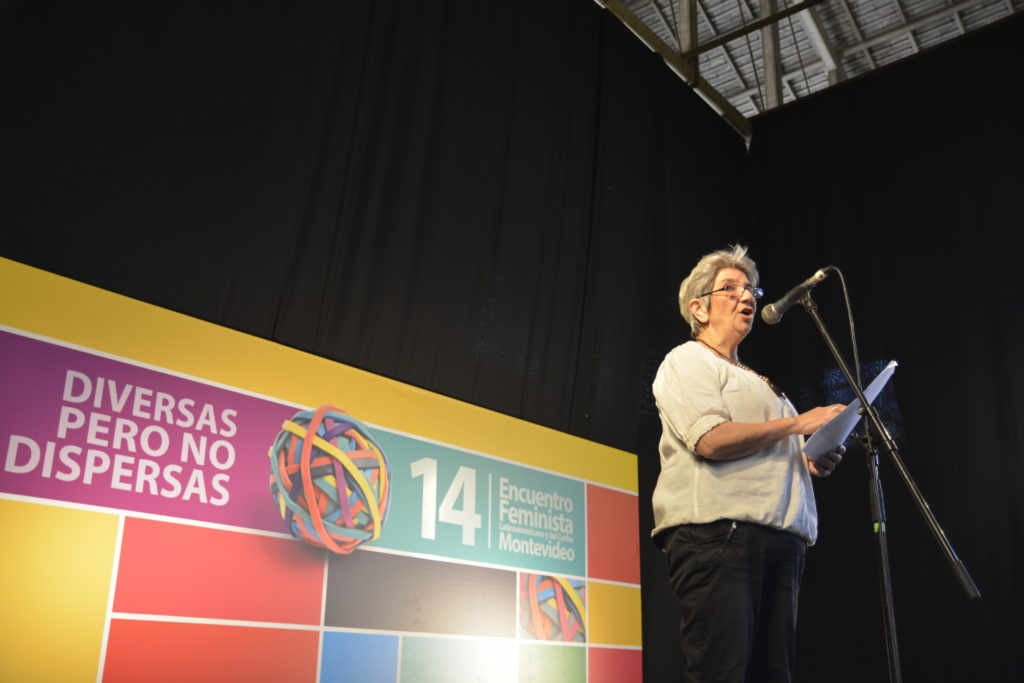 "A short, gray-haired white woman wearing glasses, a white shirt and black pants. She is speaking into the microphone, standing on a stage. Behind her is a large banner that reads, in Spanish, ""14th Montevideo Feminist Meeting - Diverse but not Divided."""