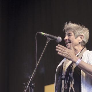 Una mujer blanca, pelo canoso y corto, lleva una camisa negra y chaqueta blanca, está de perfil, hablando al micrófono. Atrás, una cortina negra.